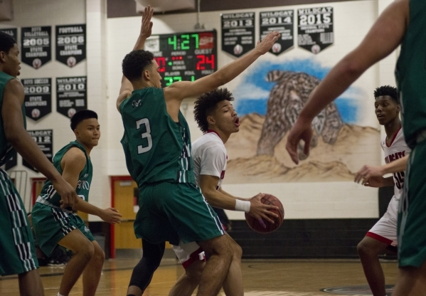 Las Vegas' Donovan Joyner (12) works the ball around Rancho's Chrys Jackson (3) during the Las Vegas Prep Championship basketball tournament at Las Vegas High School in Las Vegas on Tu ...