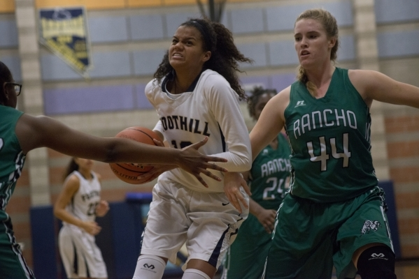 Foothillís Rae Burrell (12) works the ball toward the basket as Rancho's Samantha Pochop (44) defends during their game at Foothill High School in Henderson on Tuesday, Jan. 5, 2016. Foot ...