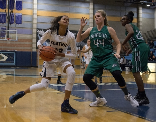 Foothillís Rae Burrell (12) works the ball around Rancho's Samantha Pochop (44) during their game at Foothill High School in Henderson on Tuesday, Jan. 5, 2016. Foothill won the game 48-4 ...