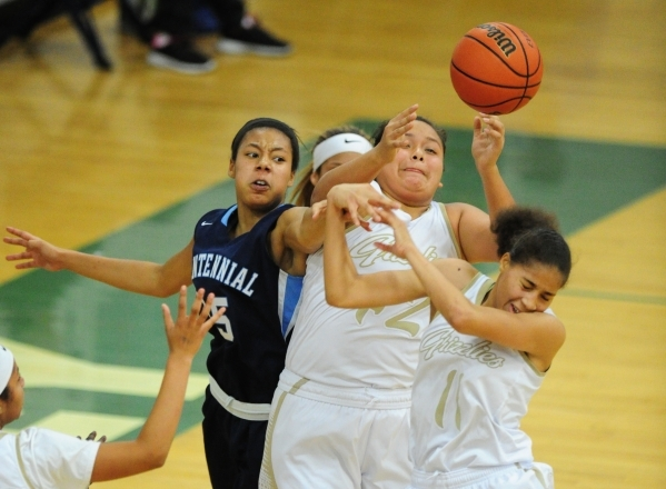 Spring Valley guard Myra Tadytin, middle, Spring Valley guard Kayla Harris (11) and Centennial guard Samantha Thomas (25) fight for a rebound in the fourth quarter of their prep girl's baske ...