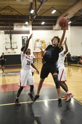 Green Valley's Xavier Jarvis (32) goes up for a lay-up against Las Vegas defenders Eric Hill (20) and Dartanion Myers (32) during their basketball game played at the Las Vegas High School gy ...