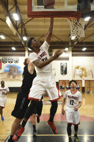 Las Vegas' Marquise Raybon (34) goes up for a lay-up against Green Valley defenders during their basketball game at the Las Vegas High School gym on Monday, Jan. 18, 2015. Green Valley defea ...