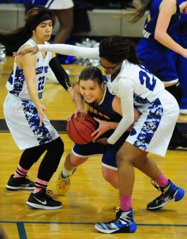 Desert Pines center Adrianne Jackson, right, attempts to steal the ball from Moapa Valley forward Kyla Shumway, center, as Desert Pines guard Heaven Heacock defends in the fourth quarter of their  ...