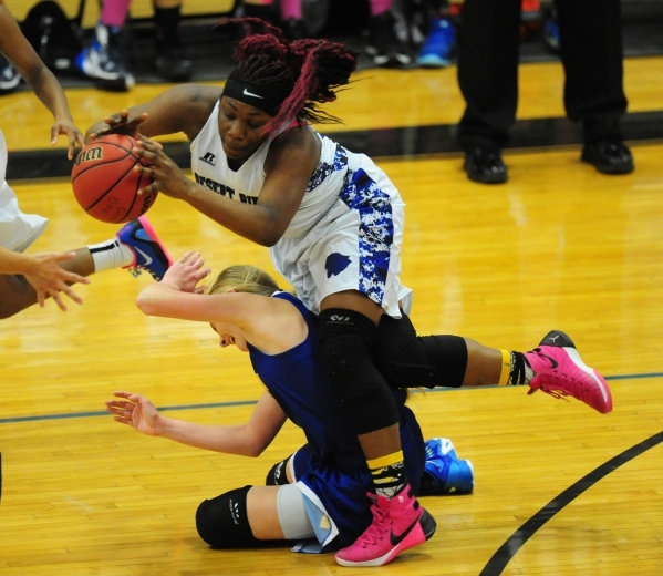 Desert Pines forward See'Airrah Evans-Collins, center, attempts to pass the ball while tripping over Moapa Valley guard Kinlee Marshall in the third quarter of their prep basketball game aga ...