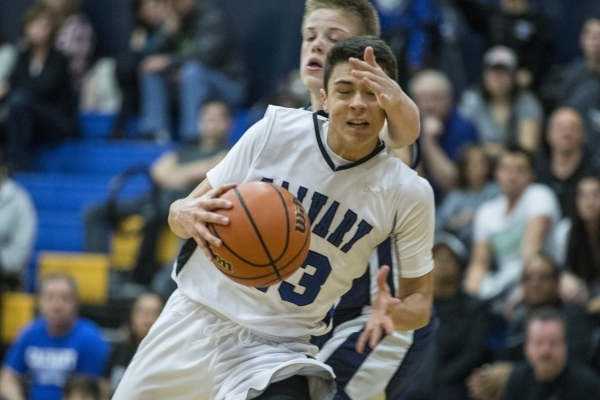 Calvary Chapel's Cameron Varela (23) takes a hit to the head as he makes his way to the basket in the boy's basketball game against White Pine at Calvary Chapel Christian School on Sat ...