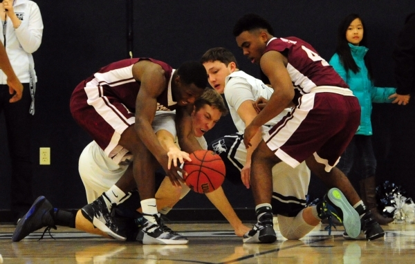 Agassi Prep guard Stephan Laushaul, left, forward Daniel Plummer (4), The Meadows guard Jake Epstein (touching the ball) and Ethan Fridman fight for a loose ball in the first quarter of their prep ...