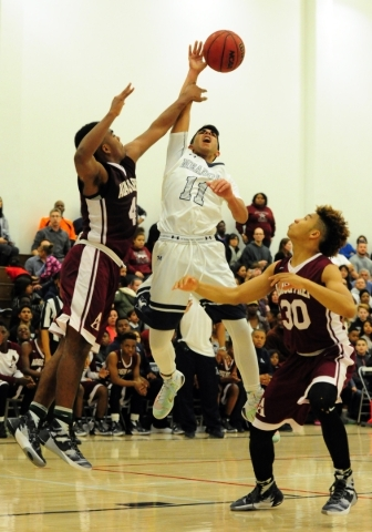 Agassi Prep forward Daniel Plummer (4) blocks the shot attempt of The Meadows guard Asheesh Chopra (11) in the second quarter of their prep basketball game at The Meadows School in Las Vegas Frida ...