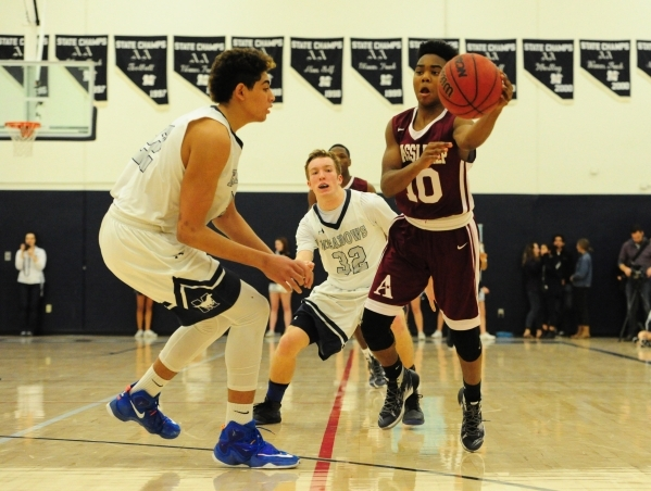 Agassi Prep guard Akeemis Williams (10) passes in front of The Meadows center Max Hisatake (22) and forward Connor Bucknam (32) in the third quarter of their prep basketball game at The Meadows Sc ...