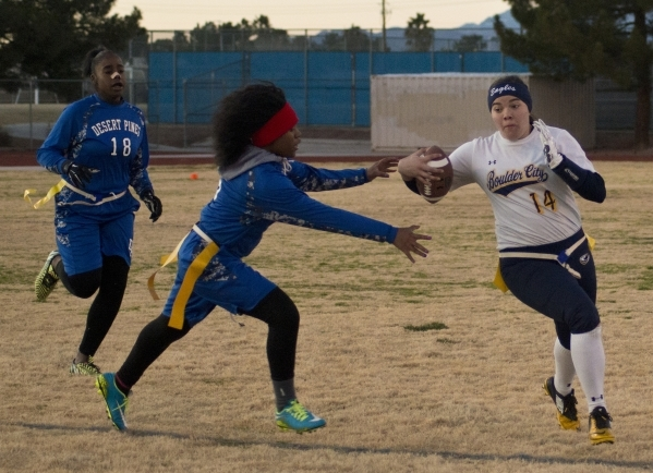 Boulder City quarterback Jeanne Carmell (14) runs by  Desert Pines' Brenda Lopez (5) during their game at Desert Pines High School In Las Vegas on Monday, Feb. 1, 2016. Boulder City won the  ...