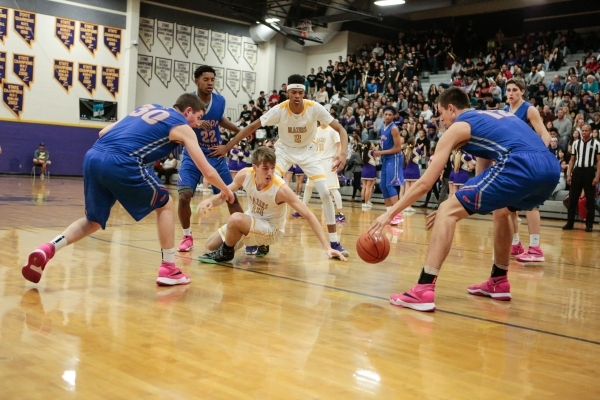 Durango senior Donte Wesley (14) along with Bishop Gorman seniors Zach Collins (12) and Travis Rice (30) reach for a loose ball during a prep basketball game at Durango High School in Las Vegas Fr ...