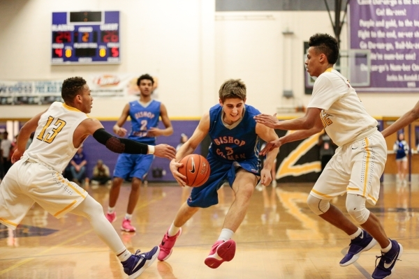 Bishop Gorman senior Byron Frohnen (3), drives between Durango junior Demetrius Valdez (13) and Durango junior Jeremie Portuondo (32) during a prep basketball game at Durango High School in Las Ve ...