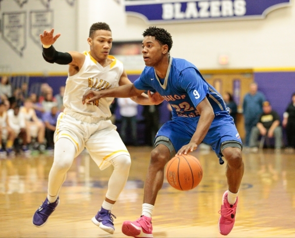 Bishop Gorman junior Christian Popoola (22) guard makes a move with the ball, while Durango junior Demetrius Valdez (13) attempts to block him, during their prep basketball game at Durango High Sc ...