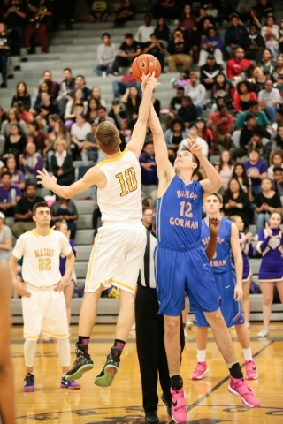 Durango senior Jason Landman (10) and Bishop Gorman senior Zach Collins (12) jump for the ball at the start of their prep basketball game at Durango High School in Las Vegas Friday, Feb. 12, 2016. ...