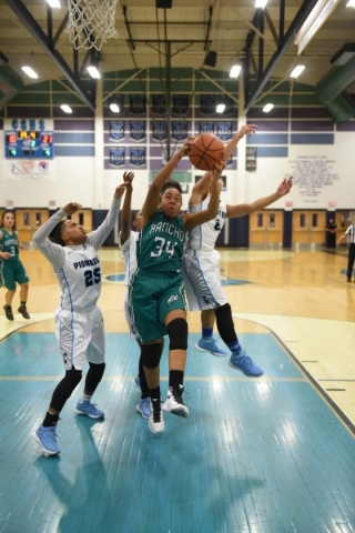 Rancho's Courtney Plumer (34) grabs a rebound against Canyon Springs defenders D'Licya Feaster (25) and Aleza Bell (2) during the Sunrise Regional quarterfinal basketball game played a ...