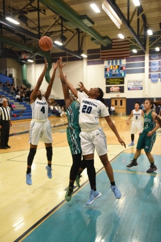 Canyon Springs Kamille Smith (4) and Alexia Thrower (20) battle for a rebound against Rancho's Kyndal Ricks (24) during the Sunrise Regional quarterfinal basketball game played at the Canyon ...