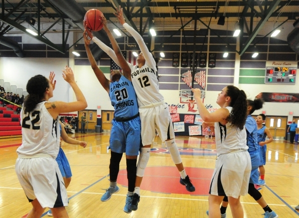 Foothill guard Rae Burrell (12) and Canyon Springs forward Alexia Thrower (20) fight for a rebound in the second quarter of their prep basketball game at Liberty High School in Henderson Thursday, ...