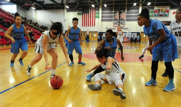Foothill guard Bri Rosales, left, picks up a loose ball in front of guard Amanda Carducci (1) and Canyon Springs forward Alexia Thrower (20) in the third quarter of their prep basketball game at L ...