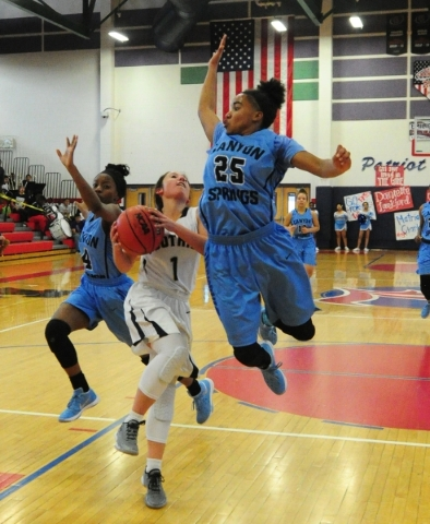 Foothill  guard Amanda Carducci (1) goes up for a shot while Canyon Springs guard D'Licya Feaster (25) and forward Kamile Smith (4) defend in the third quarter of their prep basketball game  ...