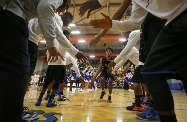 The Desert Pines High School high-fives Desert Pines High School junior Trevon Abdullah (3) as he is introduced during the I-A Southern boys basketball final at Desert Pines High School in Las Veg ...