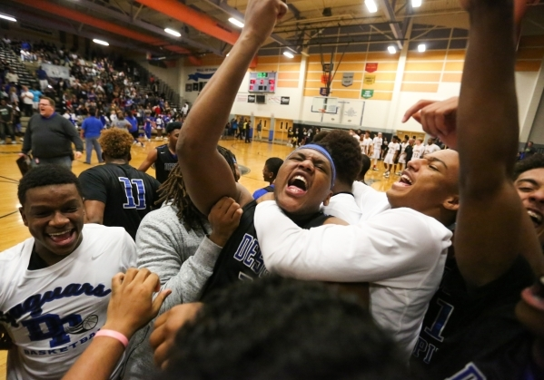 Desert Pines High School jr. Jalen Graves (12), center, is mobbed by teammates after beating Clark High School 47-42 in the I-A Southern boys basketball final at Desert Pines High School in Las Ve ...