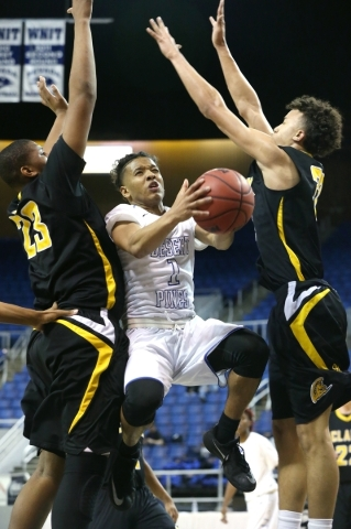 Desert Pines' Capri Uzan drives through Clark defenders Antwon Jackson, left, and Ian Alexander during the NIAA Division I-A state basketball championship in Reno, Nev. on Saturday, Feb. 27, ...