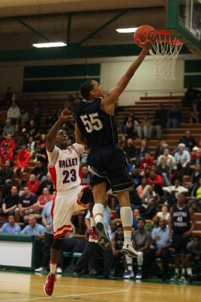 Canyon Springs guard Jordan Davis soars to the basket past Valley guard Nick Brannon in the Pioneers' 81-74 win in the Sunrise Region title game on Feb. 15. Davis averaged 15.4 points in five va ...