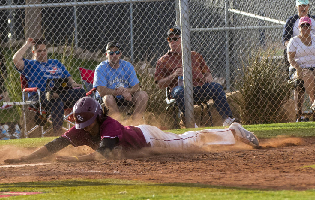Desert Oasis infielder Andrew Martinez (2) slides into home base as the winning run during the championship game of the Diamondback Kickoff Tournament against Centennial High School at Desert Oasi ...