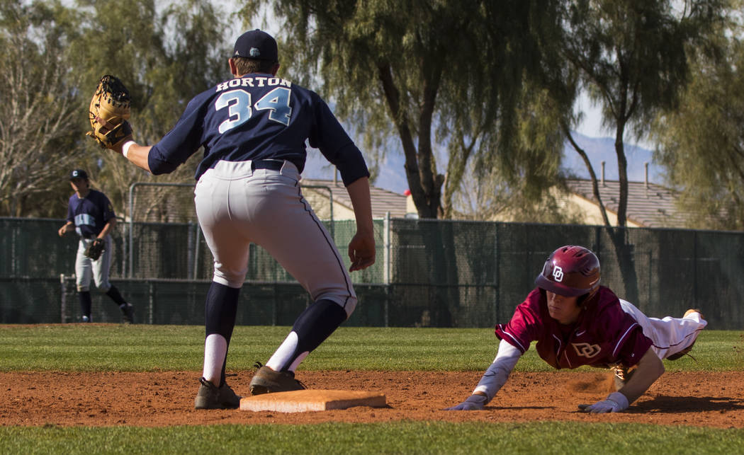 Desert Oasis shortstop Cole Schaefer (10) successfully slides back into first after trying to steal second during the championship game of the Diamondback Kickoff Tournament against Centennial Hig ...