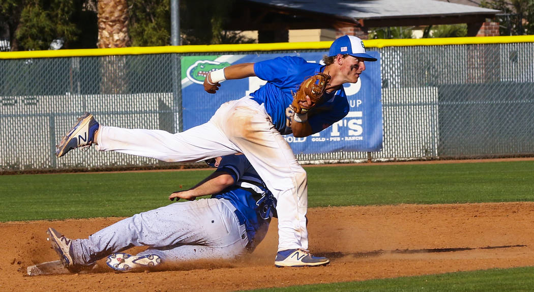 Basic third baseman Trace Evans (18) is tagged out at second base by Green Valley infielder Carter Gehlken (10) in the sixth inning during a baseball game at Green Valley High School in Henderson  ...
