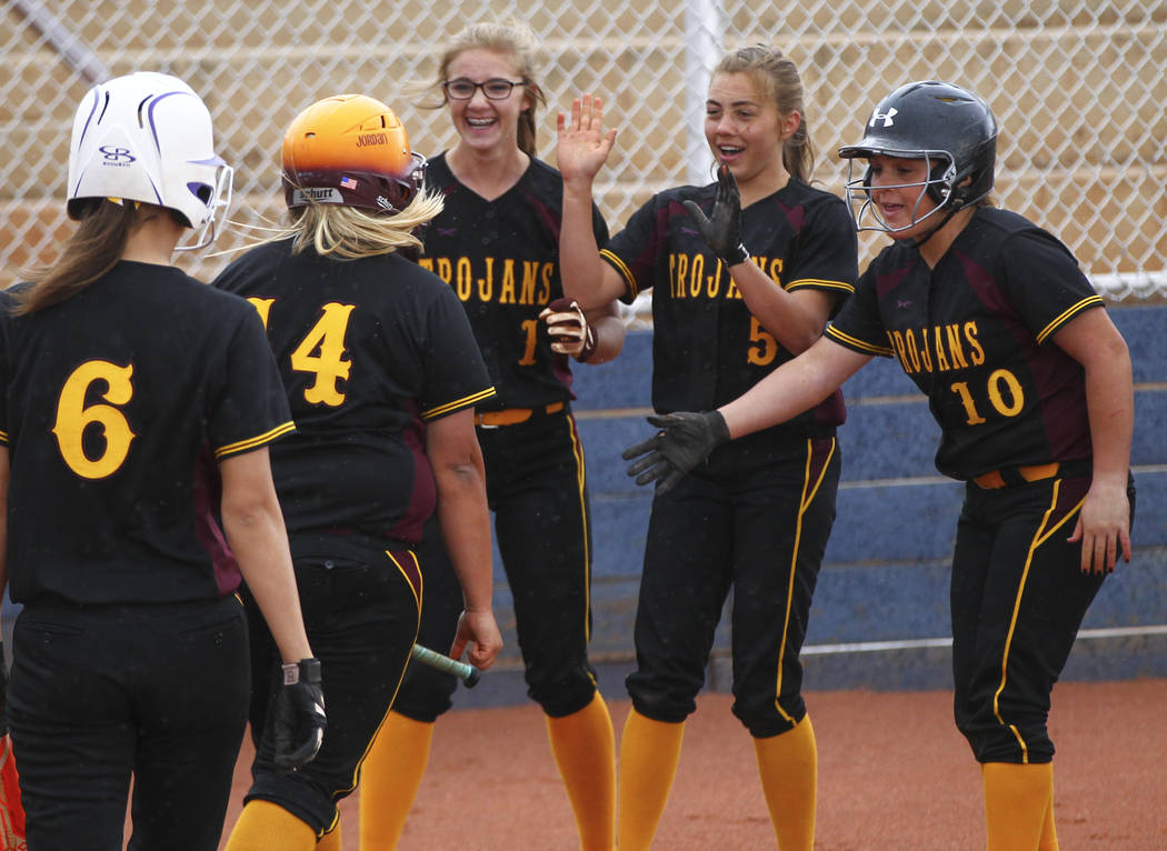 Pahrump's Jordan Egan (14) is congratulated on her home run by Terrena Martin (1), Skyler Lauver (5), and Samantha Riding (10) during a softball game at Boulder City High School in Boulder City on ...