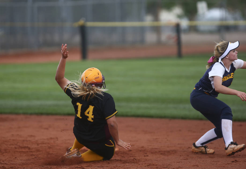 Pahrump's Jordan Egan (14) slides into second base against Boulder City's Micayla Gegen (1) during a softball game at Boulder City High School in Boulder City on Wednesday, March 22, 2017. (Chase  ...