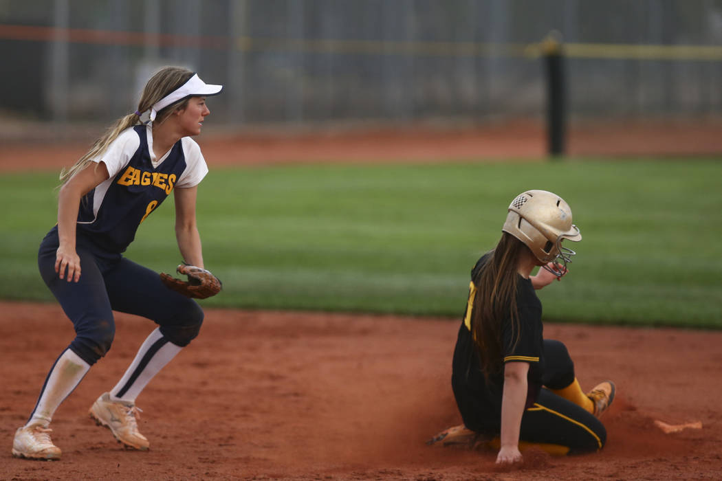 Pahrump's Jackie Stobbe (13) slides into second base past Boulder City's Ashley Wishard (8) during a softball game at Boulder City High School in Boulder City on Wednesday, March 22, 2017. (Chase  ...