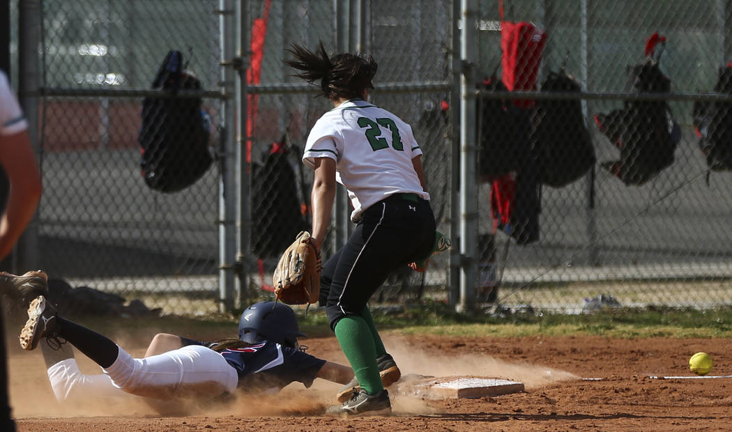 Coronado's Tatum Spangler (5) slides back into third base to stay safe as Rancho's Katerina Anthony (27) misses the throw during a softball game at Rancho High School in Las Vegas on Thursday, Mar ...
