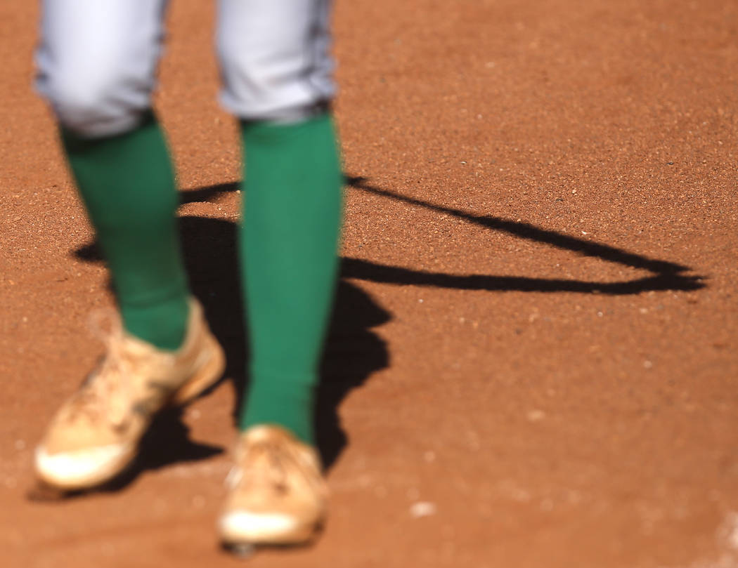 The shadow of a Palo Verde athlete is seen as she stretches before her turn at bat during the second inning of a high school softball game against Centennial at Palo Verde High School on Monday, A ...