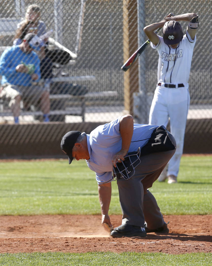 An umpire dusts off home plate as Cimarron-Memorial's Jackson Folkman (6) approaches the plate during the third inning of a high school baseball game at Cimarron-Memorial High School on Thursday,  ...