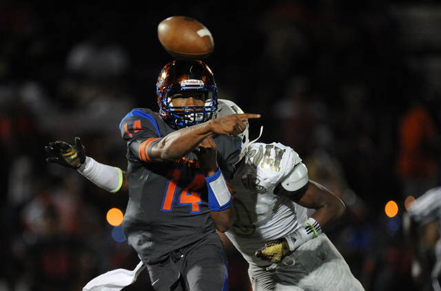 Bishop Gorman quarterback Dorian Thompson-Robinson (14) passes the ball while on being chased by Long Beach Poly Jackrabbits cornerback Davir Hamilton (9) in the fourth quarter of their prep footb ...