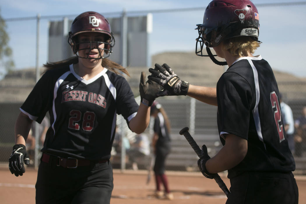 Desert Oasis senior Scarlett Hurtado, left, high-fives teammate senior Meagan Anders, right, after getting a run during a game against Durango at Desert Oasis High School on Tuesday, April 25, 201 ...