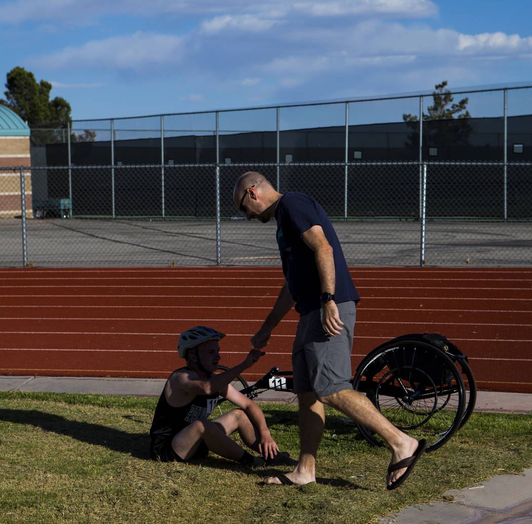 Palo Verde's Ben Slighting, who competes in a wheelchair, fist bumps his dad, Brad, after the 1600-meter run during a track and field meet at Centennial High School in Las Vegas on Friday, April 2 ...