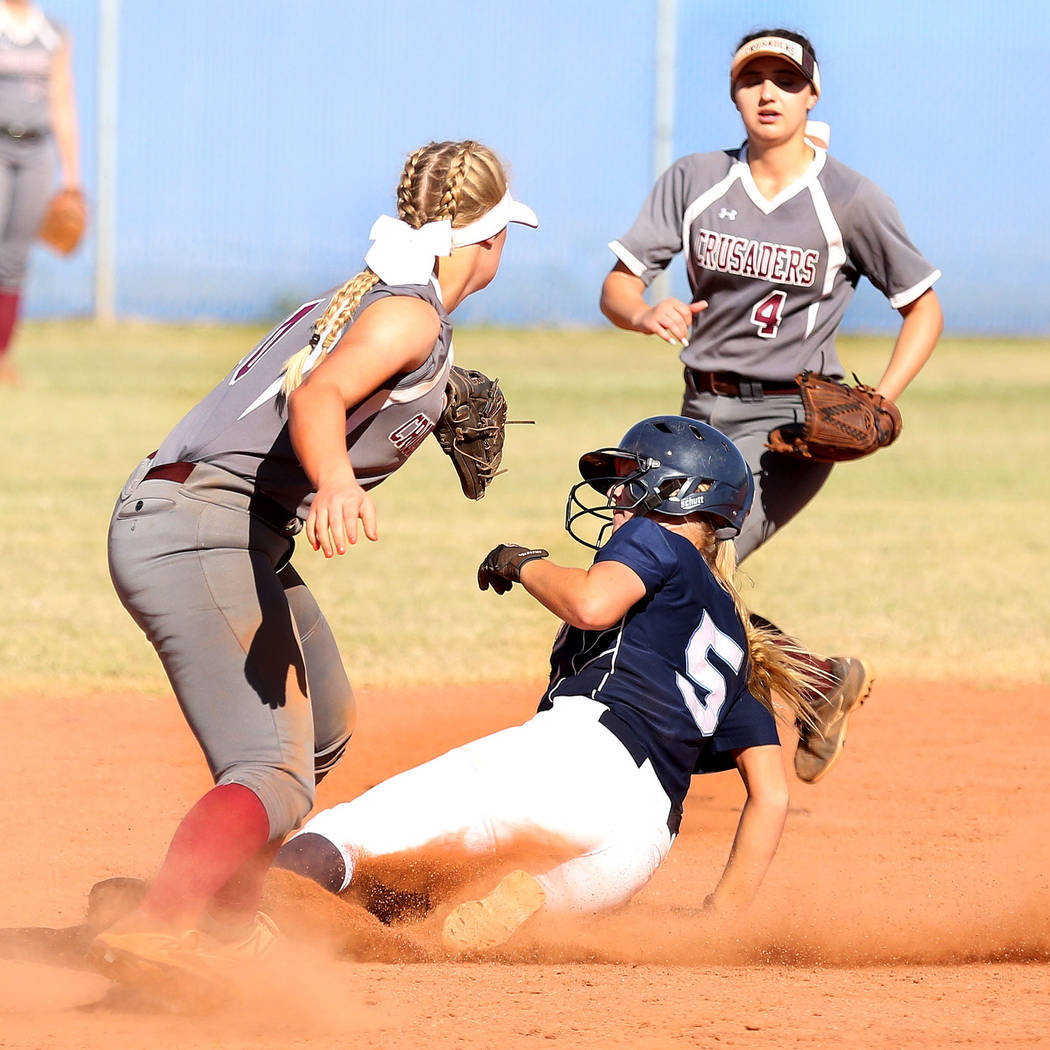 Centennial's Seanna Simpson (5) successfully slides to second base against Faith Lutheran's Maggie Whipple (10), left, and Ryleigh Gilchrist (4) at Centennial High School in Las Vegas, Wednesday,  ...