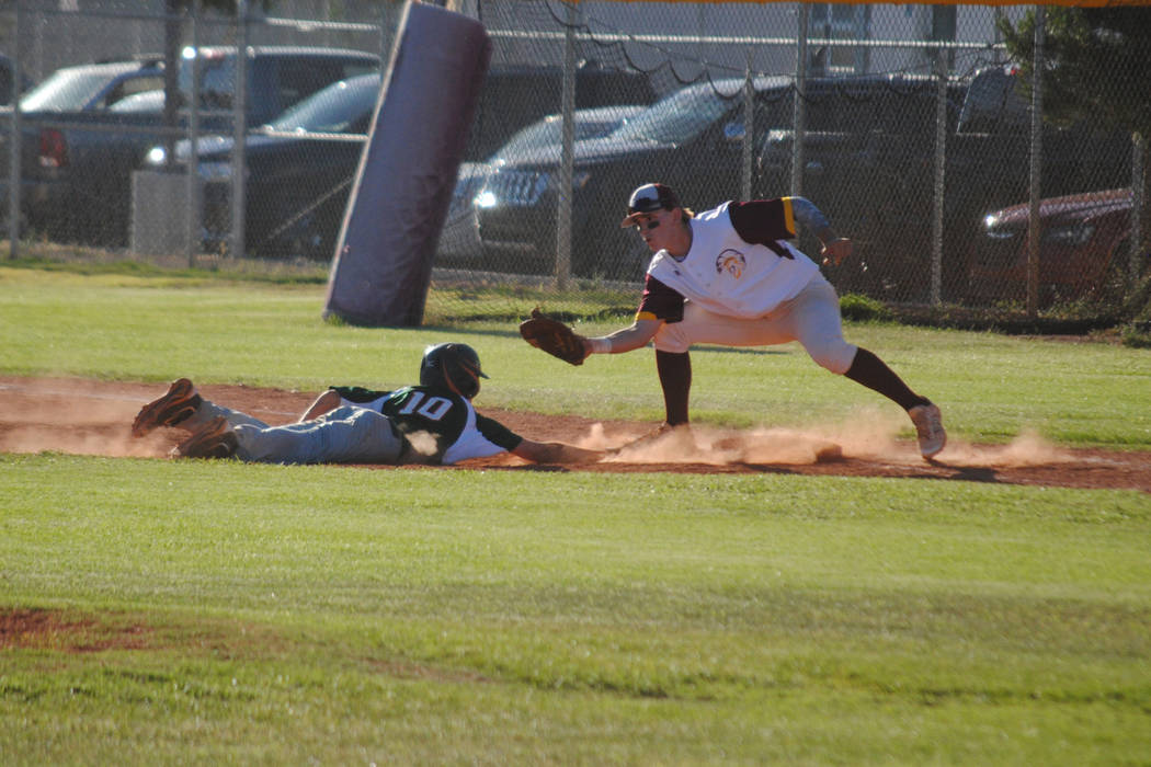 Mojave's Scott Wilson dives safely back into first base as Pahrump Valley's Parker Hart applies the tag at Pahrump Valley High School, Thursday, May 4, 2017. The Trojans won 5-2 to claim the Class ...