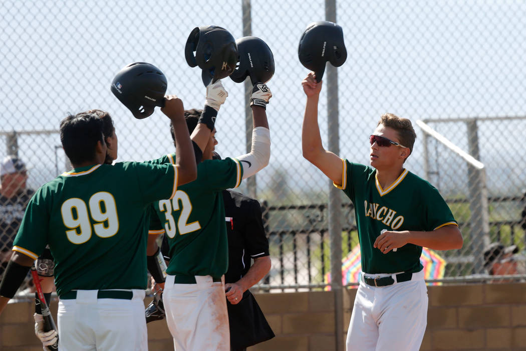 Rancho's Joseph Walls, right, celebrates with his teammates Jimmy Gamboa (99) and Adrian Williams (32) after scoring in the first inning of a state play-in baseball game against Centennial at Las  ...