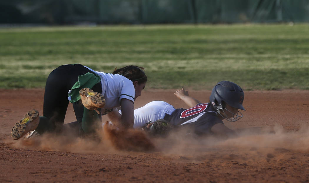 Coronado's Taylor Okamura (10) avoids getting tagged out by Rancho's Gianna Carosone (66) at second base during a softball game at Rancho High School in Las Vegas on Thursday, March 23, 2017. Coro ...