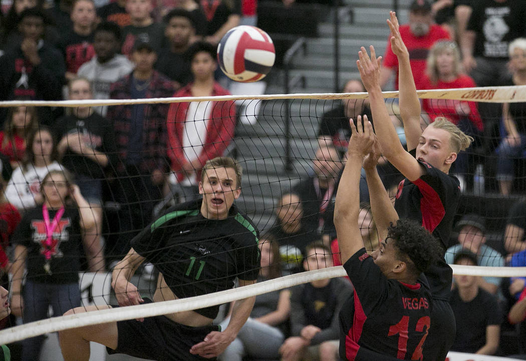 Palo Verde junior Stephen Banks (11) hits the ball over the net as Las Vegas players attempt to block during the Class 4A state volleyball final at Chaparral High School on Wednesday, May 17, 2017 ...