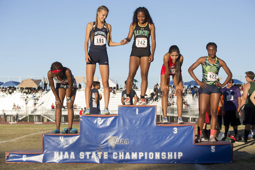 Centennial senior Karina Haymore (191), who placed second, holds hands with Rancho junior Gizelle Reid (742), who placed first, after the girls 4A 400-meter dash at the NIAA State Track & Fiel ...