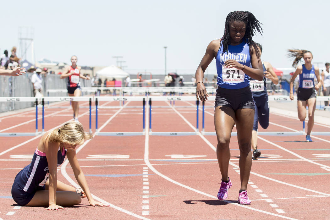 Centennial senior Talie Bonds falls to the ground next to McQueen junior Destiny Tolliver after the girls 300-meter hurdles during the NIAA State Track & Field Championships at Foothill High S ...