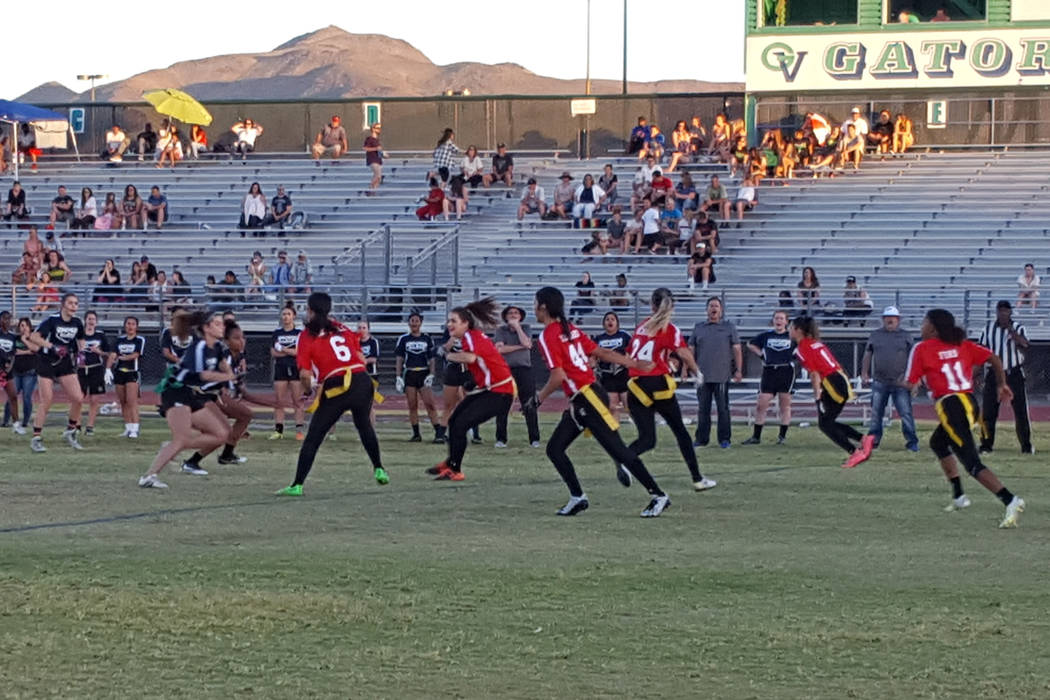 Centennial's Denae Benites (24) takes the handoff from Cimarron-Memorial's Tiarra Del Rosario (44) during the Class 4A flag football all-star game at Green Valley High on May 23, 2017. (Damon Seit ...