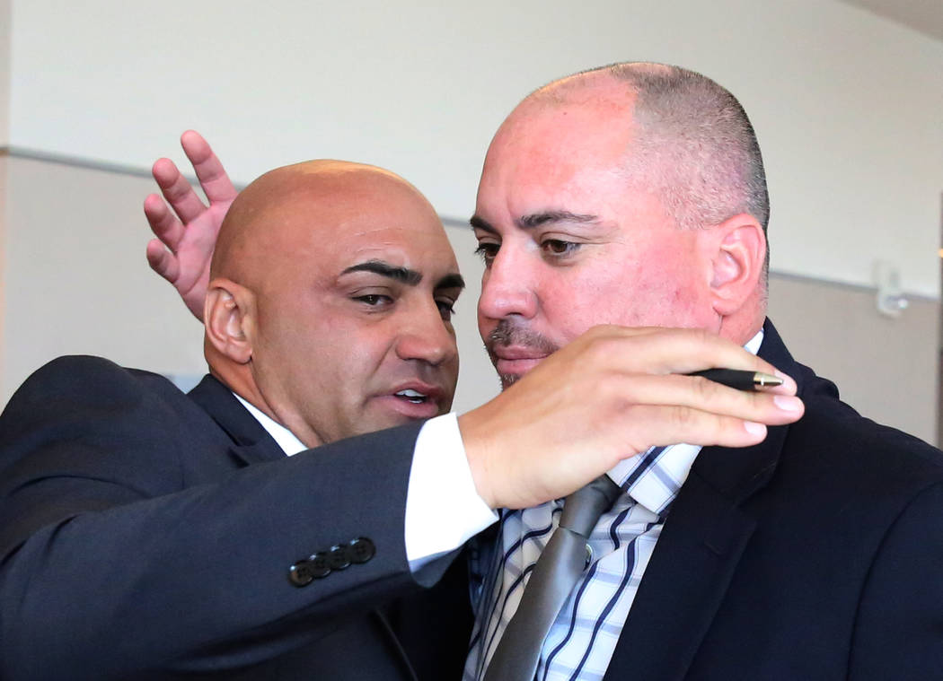 Kenny Sanchez, Bishop Gorman's head football coach, left,  hugs his brother Tony Sanchez, UNLV head coach, after being found not guilty of domestic violence against his ex-girlfriend, at the Regio ...