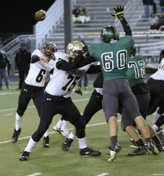 Faith Lutheran quarterback Jacob Deaville (6) unloads a pass as teammate Austin Prather (75) blocks Churchill County's Justin Hatfield (60).
