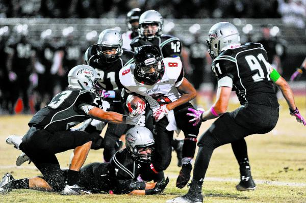 Las Vegas receiver Corey Sinceno (8) is brought down by a host of Green Valley defenders including Albert Lake (23) and Derrick Webb (91) on Friday.