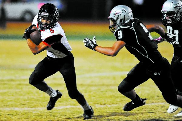 Las Vegas back Andrew Moreland (5) looks for running room against Green Valley's Jairo Rebolledo (9) on Friday.